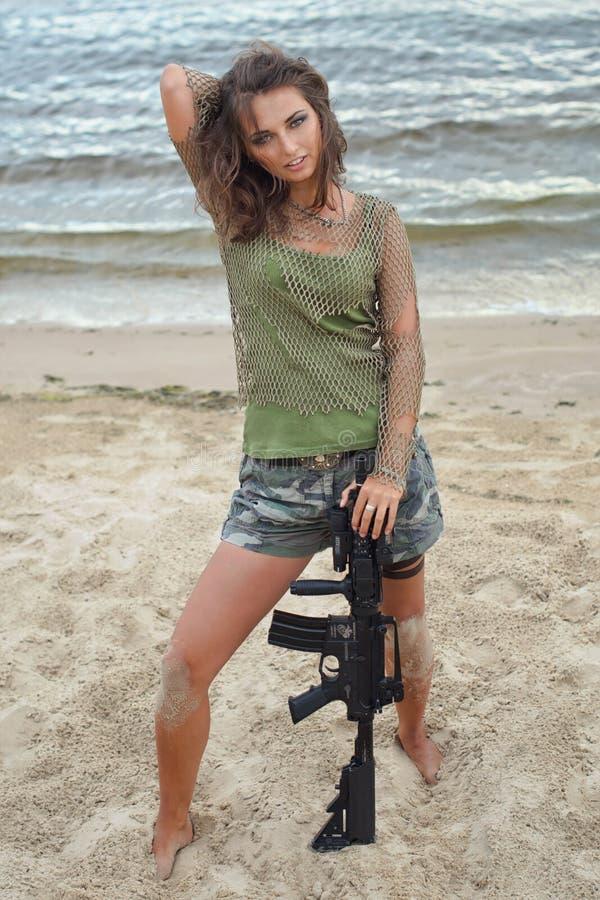 Girl with a rifle on the beach stock photos