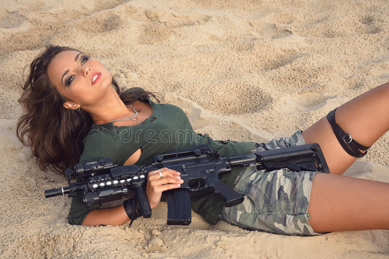 Girl with a rifle on the beach royalty free stock photos