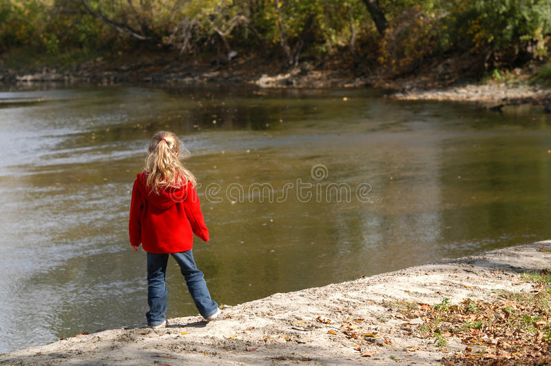 Girl On A Riverbank. A young girl stands on a riverbank watching the water flow past her stock photography