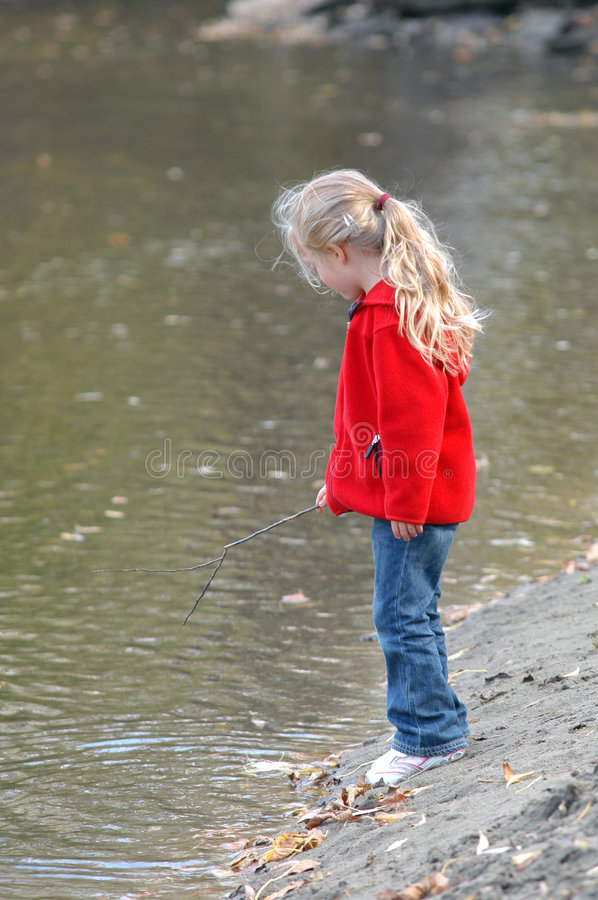 Girl on Riverbank. A young girl stands on a riverbank watching the water and leaves flow past her. She uses a stick she found to splash in the water and poke at stock photos