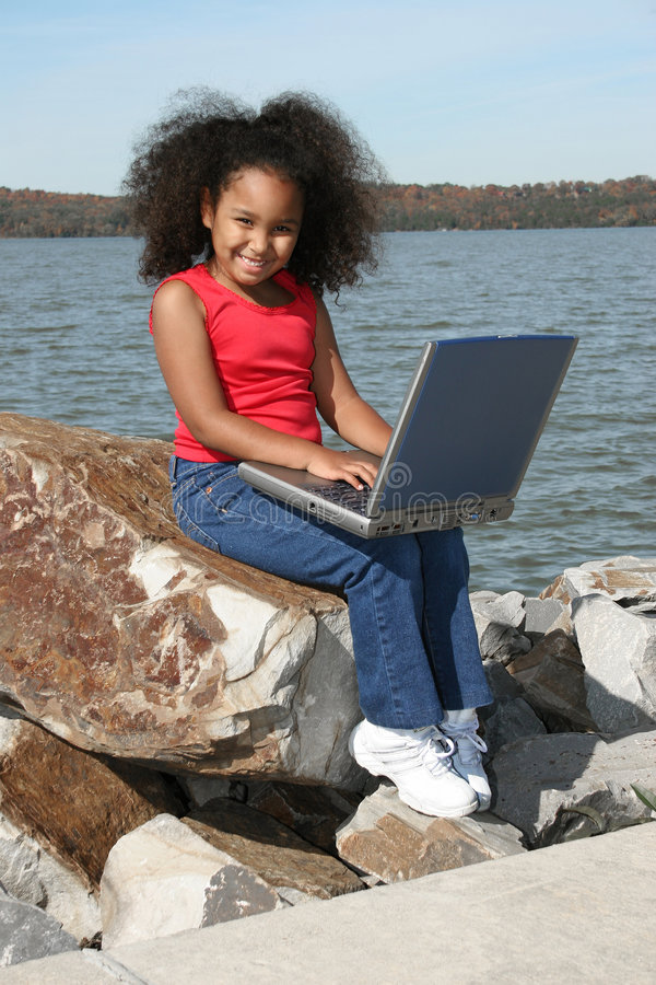 Girl on riverbank with laptop. A view of a pretty young girl, sitting on a large rock beside a river, holding a laptop computer royalty free stock image