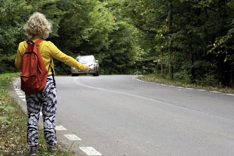 Girl on the road, auto stop, travel concept. Closeup photo of woman hitchhiking on a forest road. Traveler concept royalty free stock image
