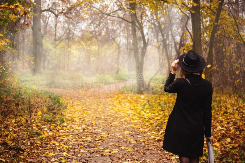 Girl on the road, back view. Woman in a black coat and hat in foggy weather stock photos