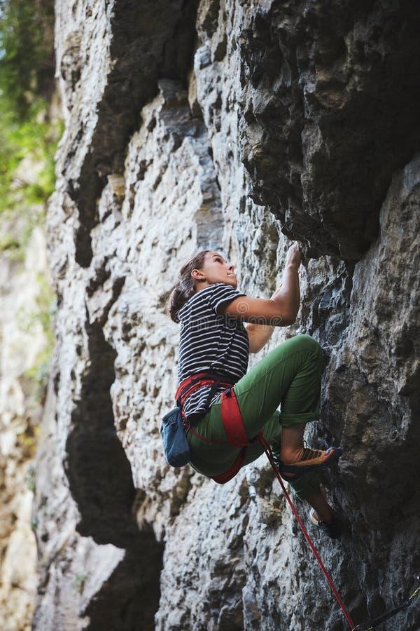 Girl rock climber climbing on the cliff stock image