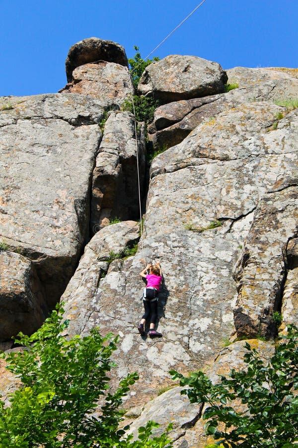 Girl rock climber climbs on rock stock photos