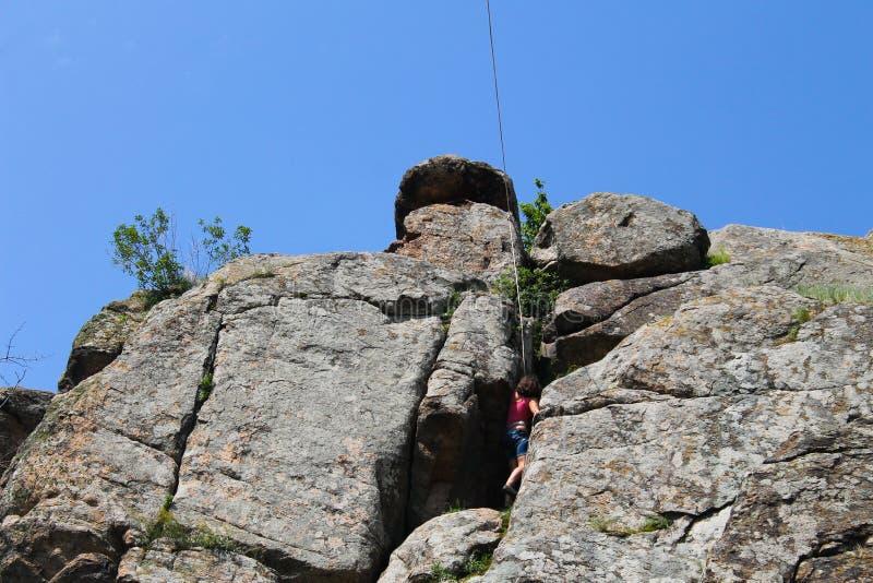 Girl rock climber climbs on rock. Girl rock climber climbs on a rock stock photography