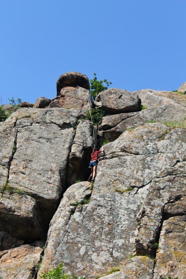 Girl rock climber climbs on rock royalty free stock photography