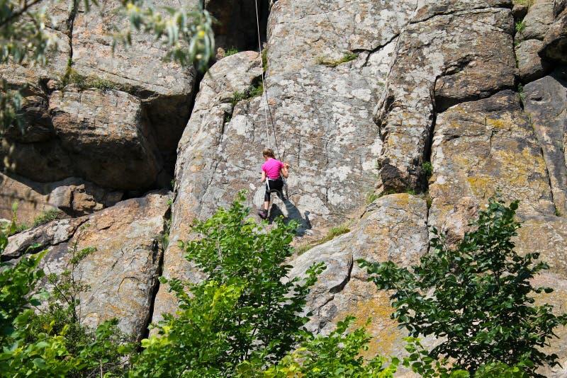 Girl rock climber climbs on a rock stock photography