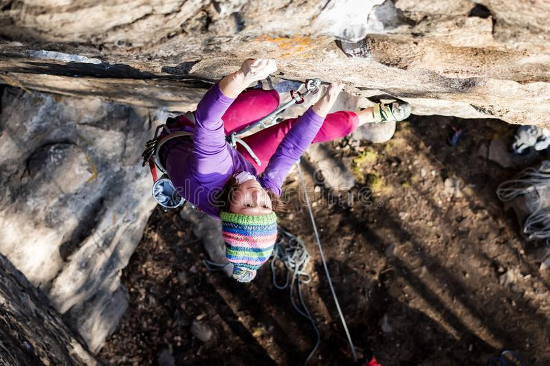 Girl rock climber climbs on the rock with the lower insurance men in colorful clothes and a hat in the fall stock images