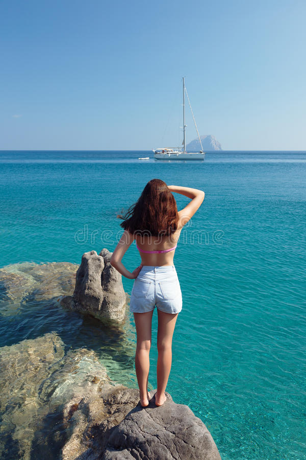 Girl on the rock looking to the yacht on sea royalty free stock photo
