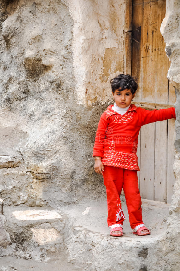 Girl in rocky village in Iran. Kandovan, Iran - circa June 2011: Small girl in red clothes stands in front of her rock house in rocky village of Kandovan in Iran stock image