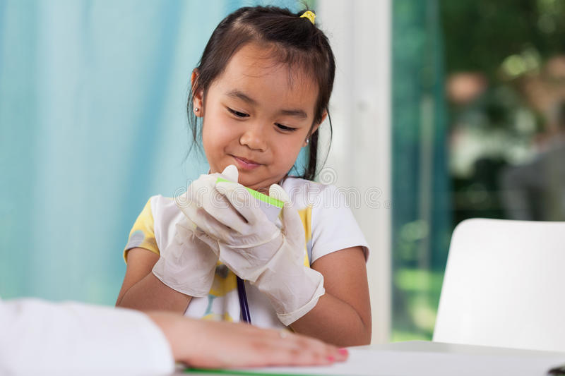 Girl in the role of doctor. Asian girl in the role of doctor stock image