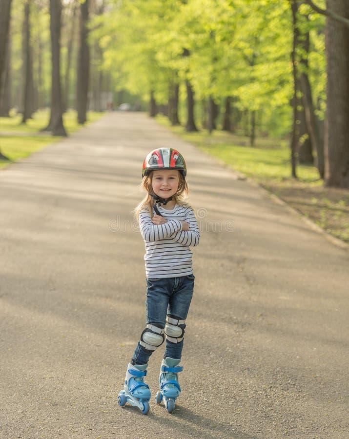 Girl roller blading, arms crossed on chest. Little girl in helmet standing in the alley, roller blading, arms crossed on chest royalty free stock photography