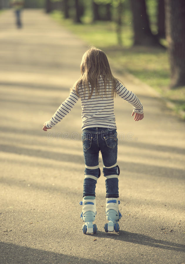 Girl roller blading in park, back to camera. Small girl roller blading in the park, back turned to camera, moving fast royalty free stock images