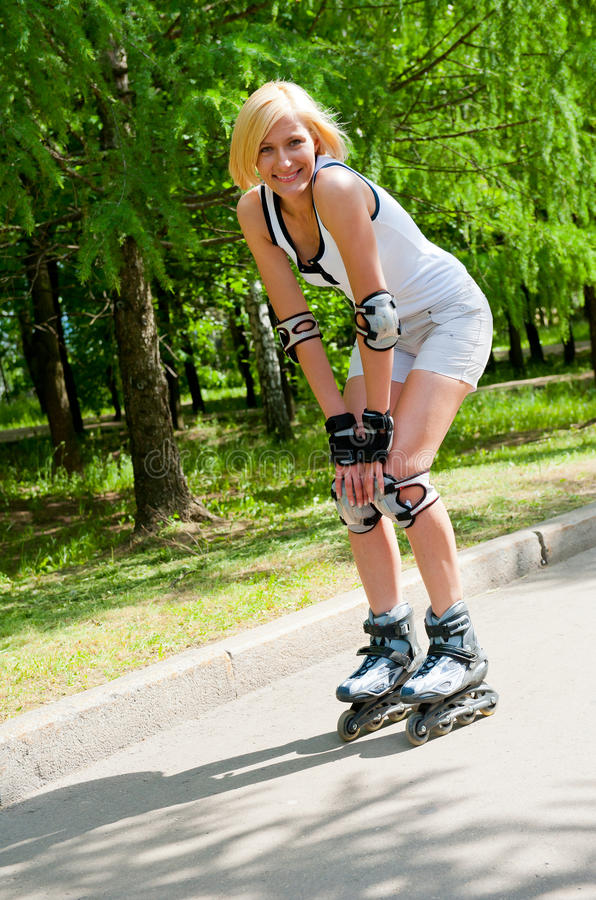 Girl roller-skating in the park royalty free stock image