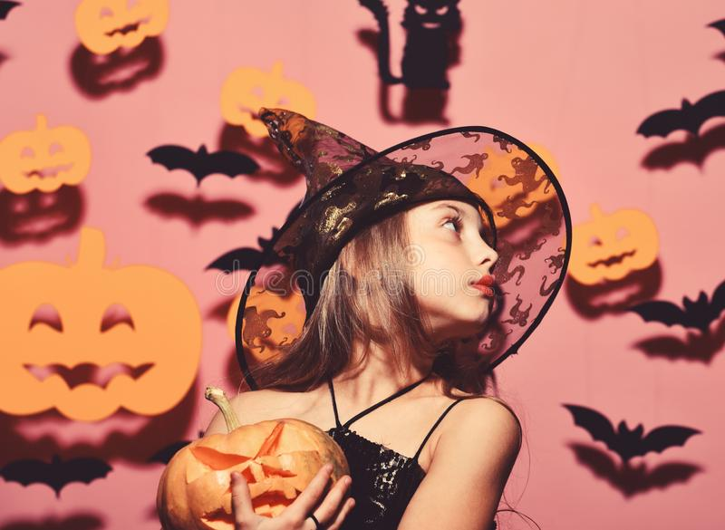 Girl with romantic face on pink background with decor. Girl with romantic face on pink background with bats and pumpkins decor. Kid in spooky witches costume stock images