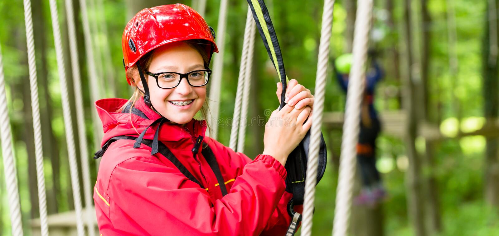 Girl roping up in high rope course. Exercising the necessary safety precautions royalty free stock photo