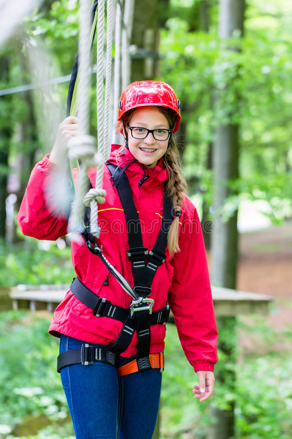 Girl roping up in high rope course. Exercising the necessary safety precautions stock images