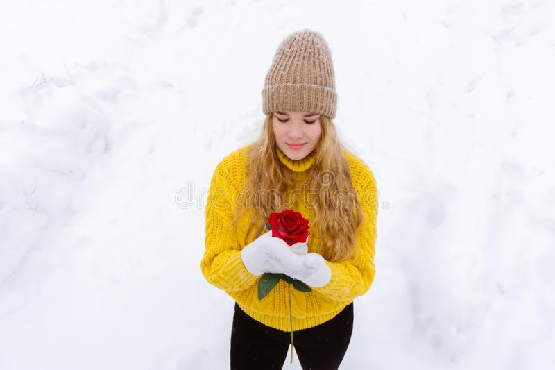 Girl with a rose on the background of snow royalty free stock photo