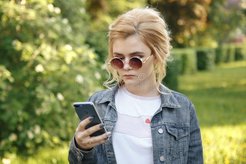 Girl with round glasses. Hair in a bun. The girl with the phone. Girl looking stock photography