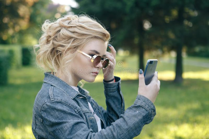 Girl with round glasses. Hair in a bun. The girl with the phone. Girl looking royalty free stock photo