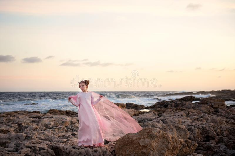 A girl in a royal crown and in a long pink dress is standing at the seashore in the rays of the rising sun and a veil is flying in royalty free stock images