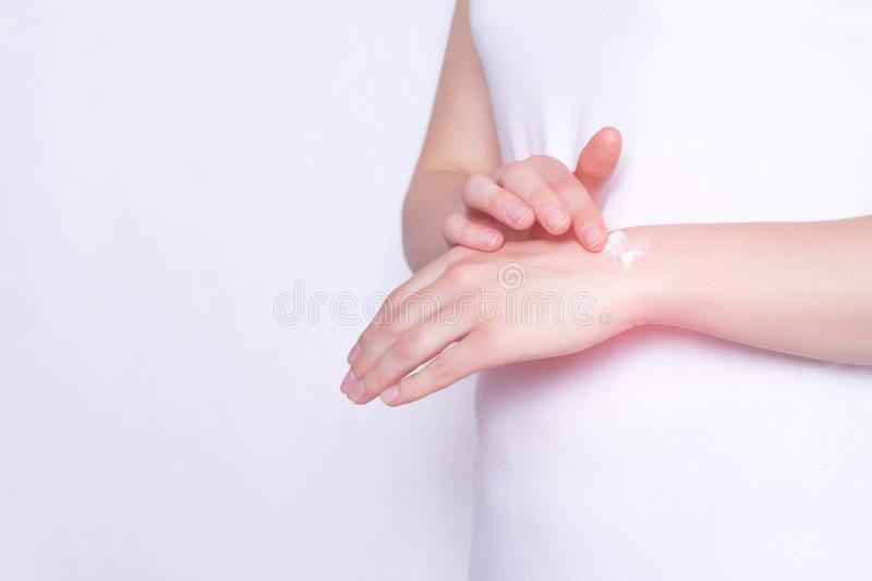The girl rubs the healing ointment into the wrist joint against pain and inflammation in the joint, White background, copy space, stock photo