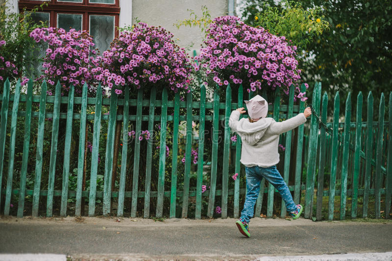 Girl run with flower on a background of green fence stock images