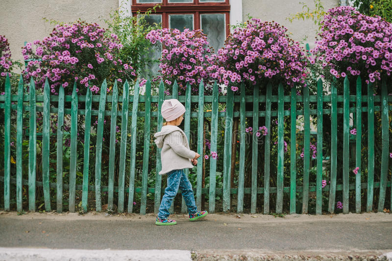 Girl run with flower on a background of green fence royalty free stock photo