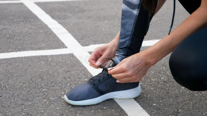 Girl runner tying laces for jogging her shoes on road in a park. stock photos