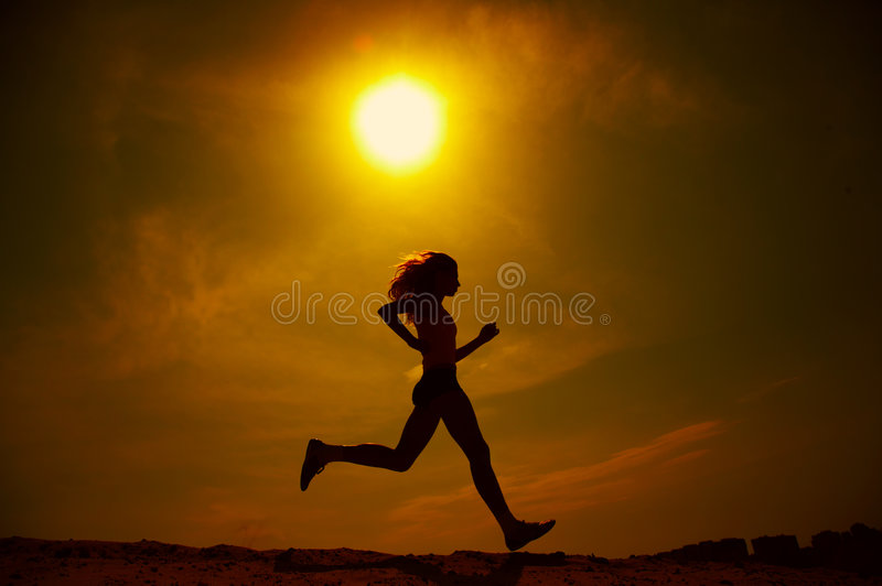 Girl running. A silhouetted view of a girl running under a hot, blazing summer sun