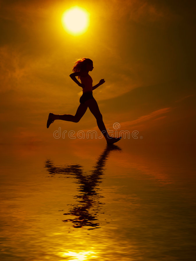 Girl running. She is silhouetted with sun overhead and reflection off ground stock photo