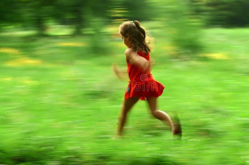 Girl running. Little girl in red dress running in nature, motion blur stock photo