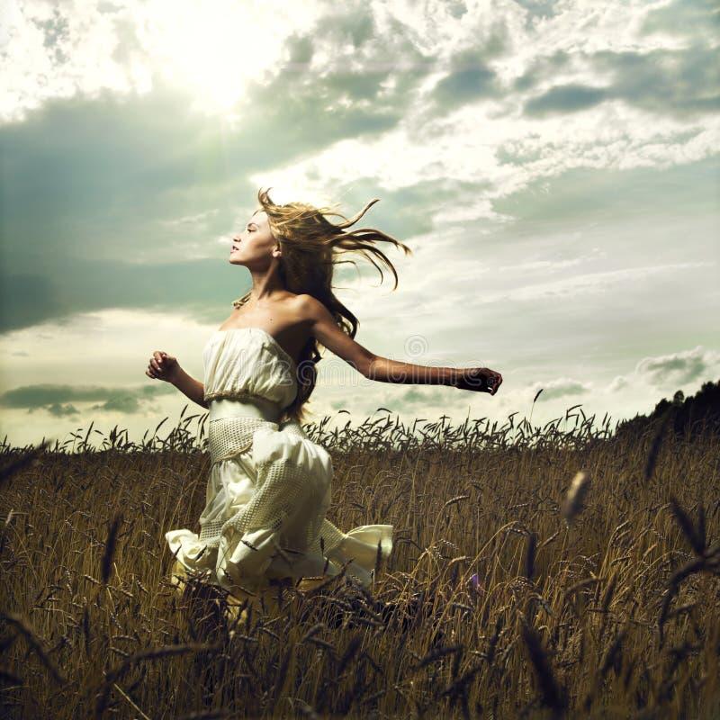 Girl running across field stock image