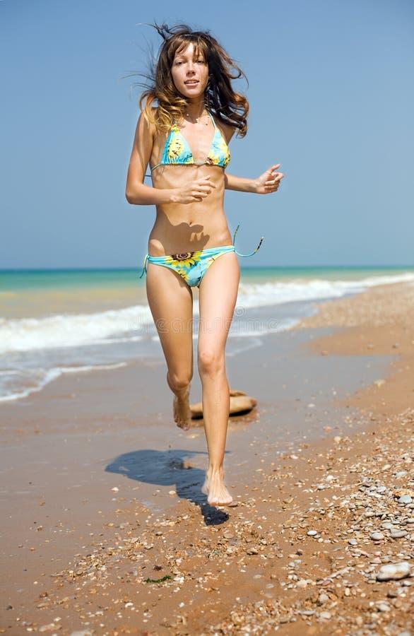Girl Running Along Seashore Stock Photos