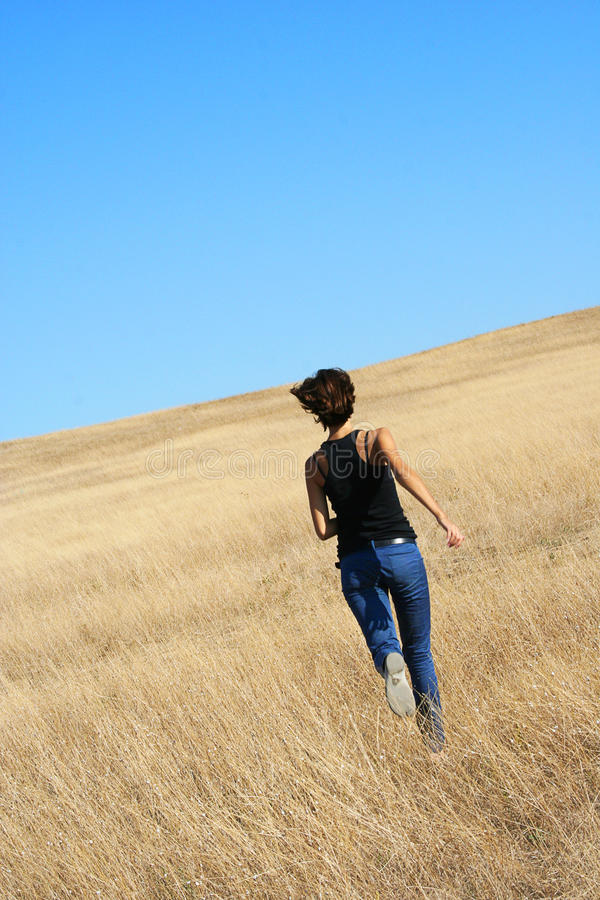 Girl running away. In the field royalty free stock images