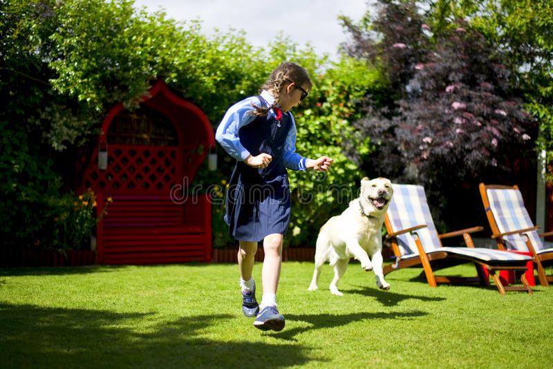 Girl running away from the dog. Small girl running away from the dog in the garden royalty free stock photo