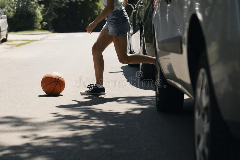 Girl running with ball on pedestrian crossing. Next to cars royalty free stock photo