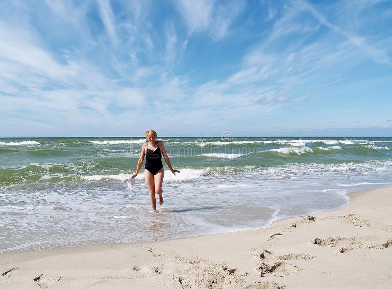 The girl running from the Baltic sea royalty free stock image