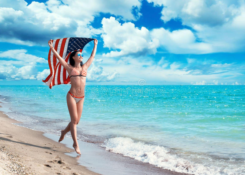 Girl running on the beach with the American flag. Happy girl in bikini running on the beach with the American flag fluttering in her hands stock images