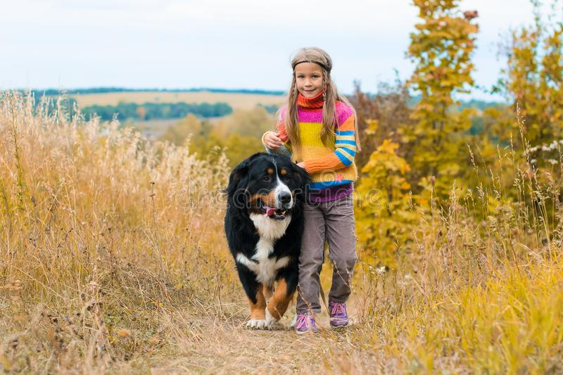 Girl running with big dog. For walk on autumn meadow royalty free stock photos