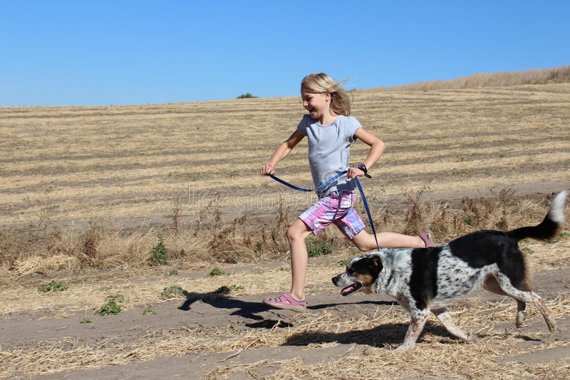 Girl Running with Dog stock photo