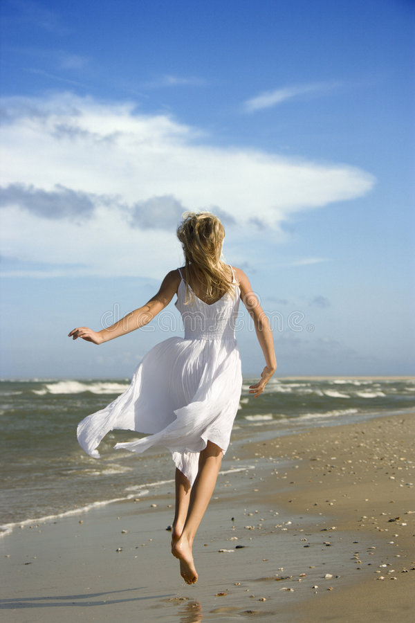 Girl running down beach. stock photos