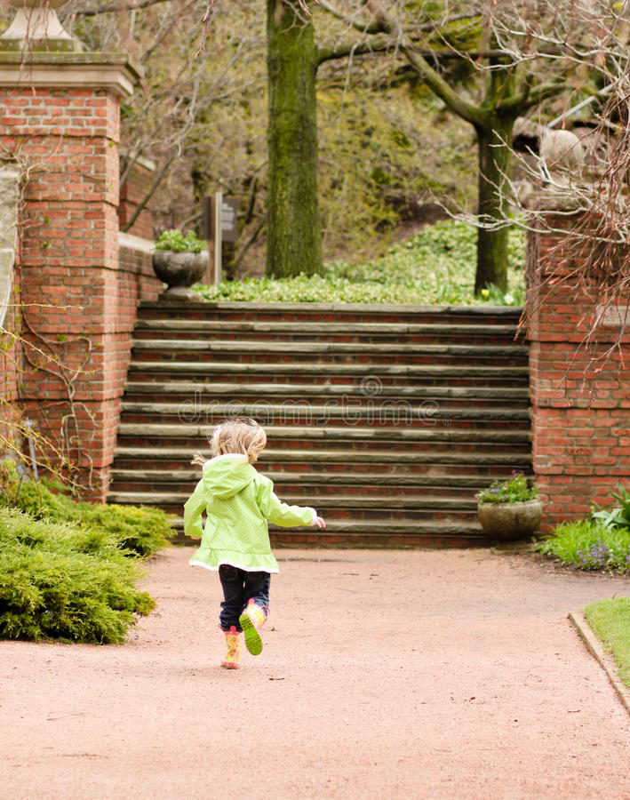 Girl running through a garden stock photo