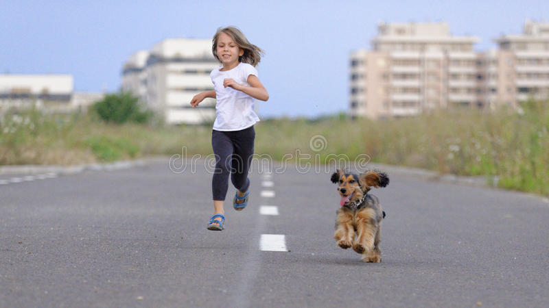 Girl running with her dog. Young athletic girl running along the road after her brown and black Cocker Spaniel puppy stock image