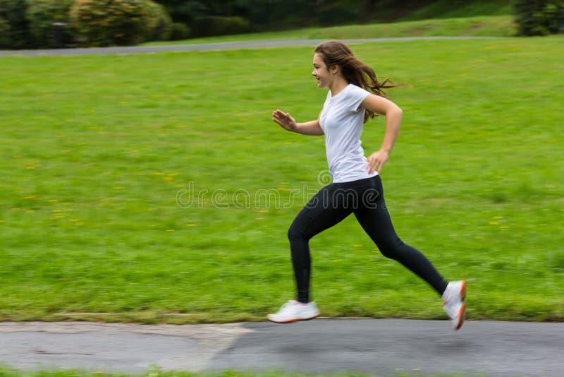 Girl running. Girl jumping on running lane in park royalty free stock photos