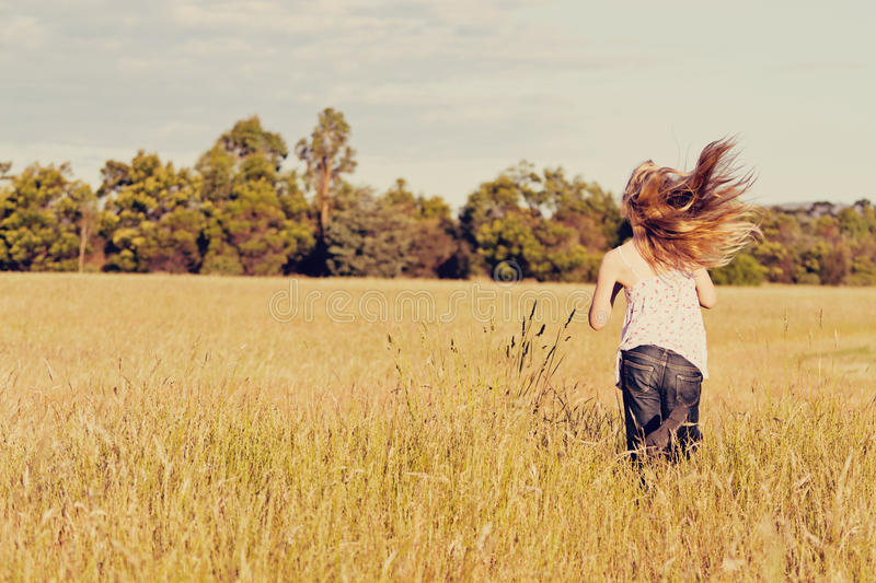 Girl running in meadow, freedom. A little girl running through a grassy field beneath the setting sun royalty free stock photo