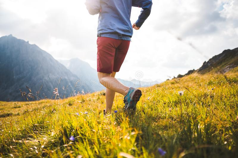 Girl Running in Mountains. Legs of Sportive Girl Running into the Sunset on a Trail in the Beautiful Mountains of the Austrian Alps stock photography