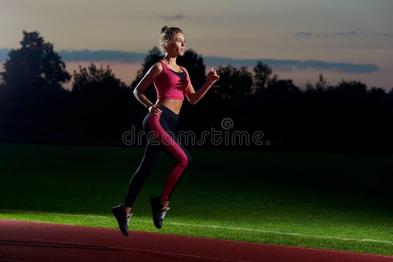 Girl running at night on stadium preparing for marathon. royalty free stock images