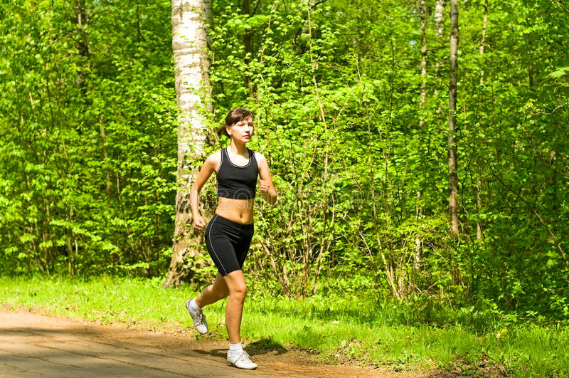 Girl running in park stock image